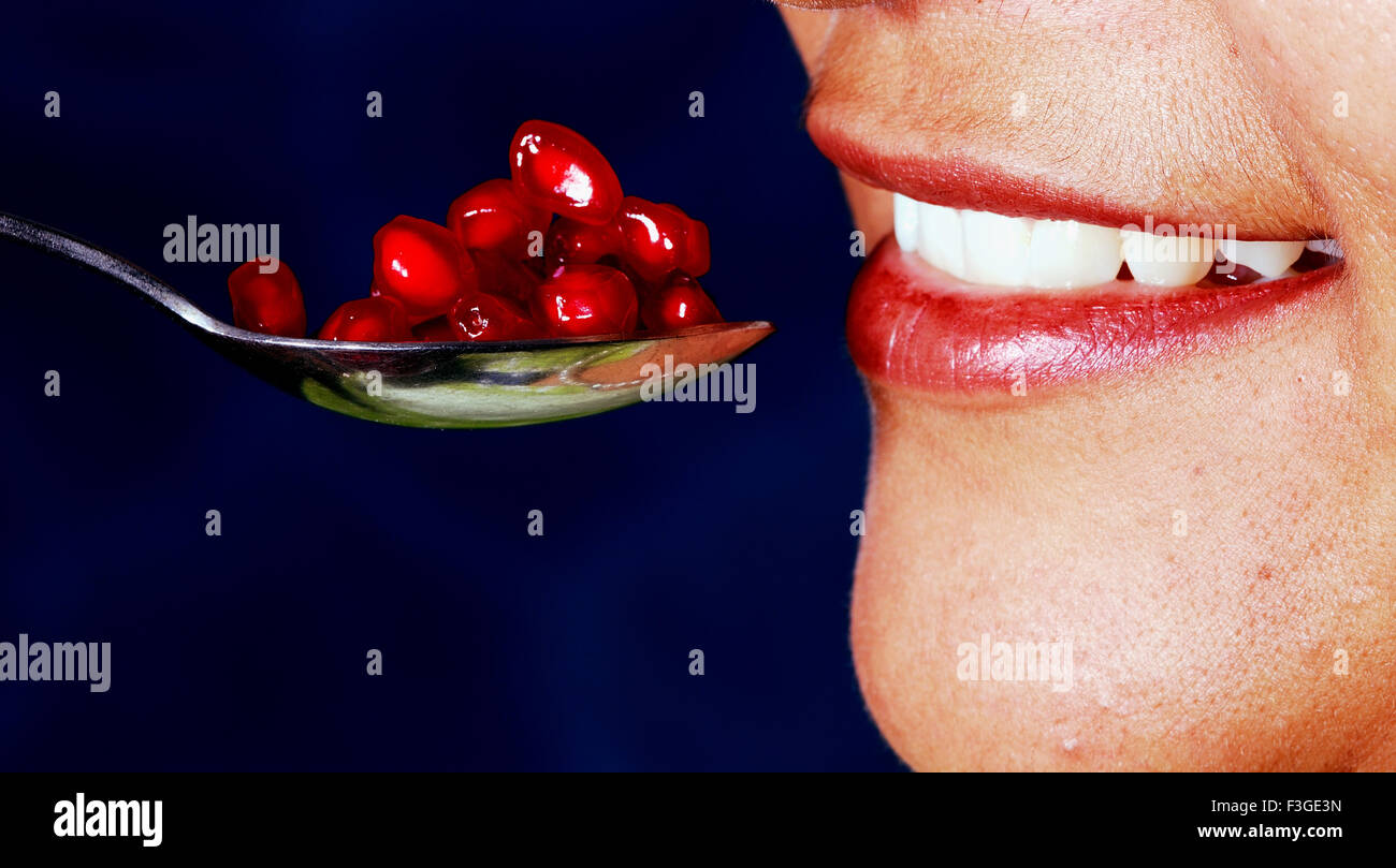Beautiful Teeth and Lips About To Fed Red Colorful Pomegranate Seeds Face is Not Full And Recognizable No MR - Stock Image