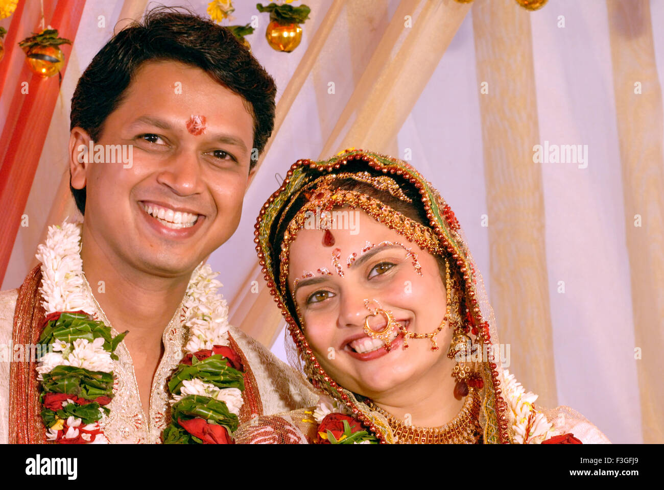 Indian Hindu Gujarati wedding bride and bridegroom looking at camera happy smiling faces - MR#364 - RMM 123501 - Stock Image