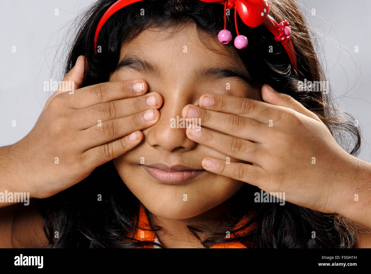 baby girl child with hands covering eyes playing hide and seek MR#152 - Stock Image