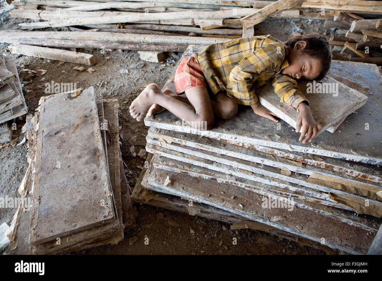 Young boy sleeping in the midst of all the construction materials ; Ahmedabad ; Gujarat ; India - Stock Image