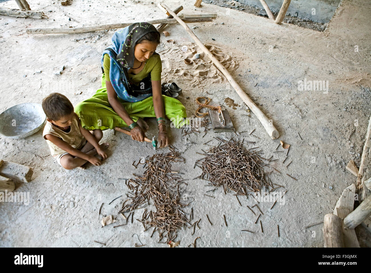 A small child accompanied by her mother at a construction site ; Ahmedabad ; Gujarat ; India - Stock Image
