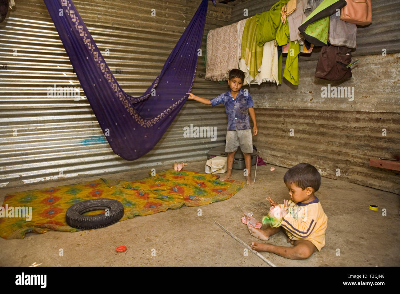Young siblings in a makeshift corrugated sheet home at a construction site ; Ahmedabad ; Gujarat ; India - Stock Image