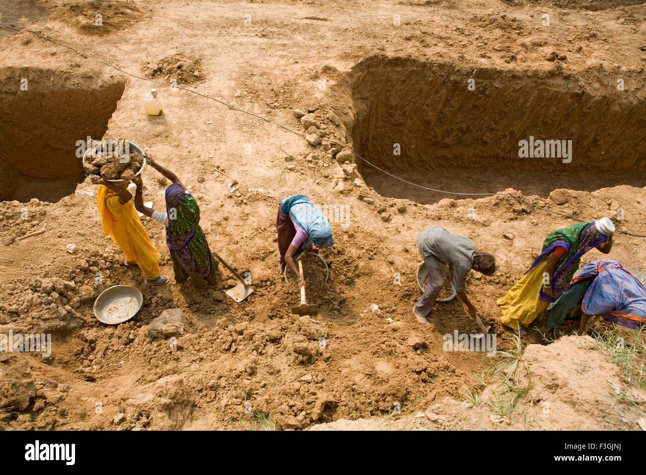 Workers at a construction site engaged in manual unskilled work ; Ahmedabad ; Gujarat ; India - Stock Image