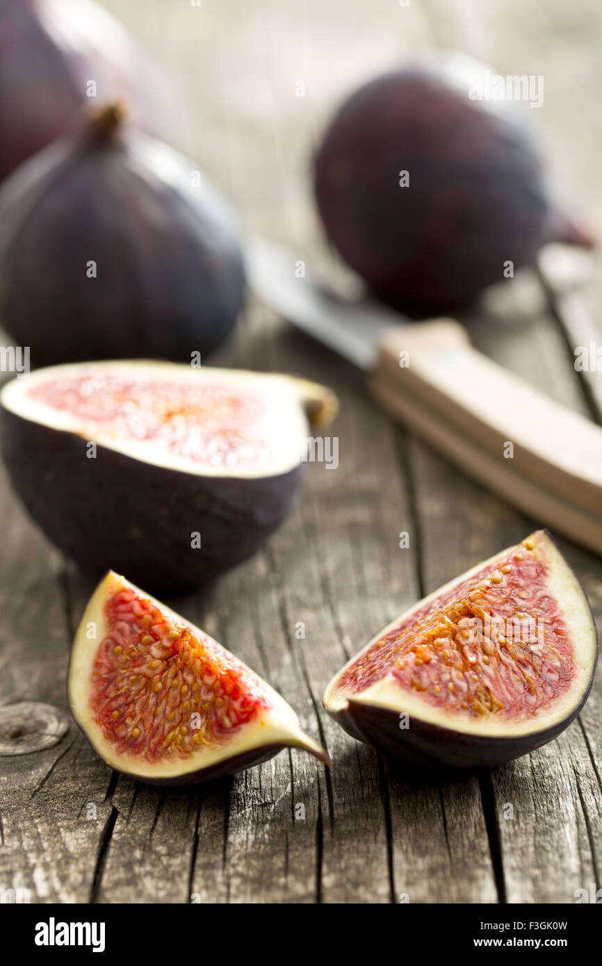 sliced fresh figs on old wooden table - Stock Image