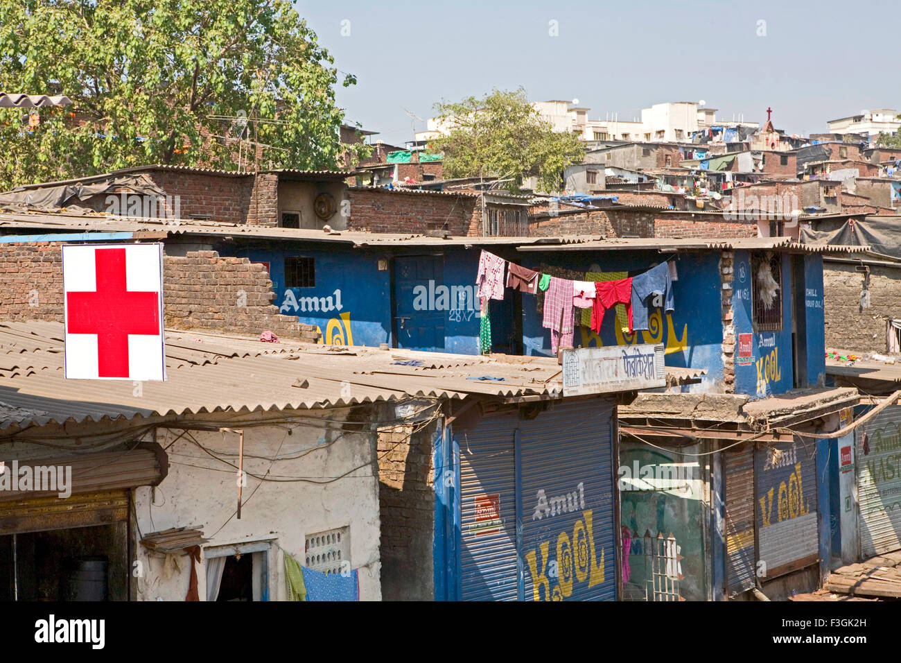 Prominent sign of doctor's clinic on roof top of slum poor living and hygienic conditions lead various diseases - Stock Image