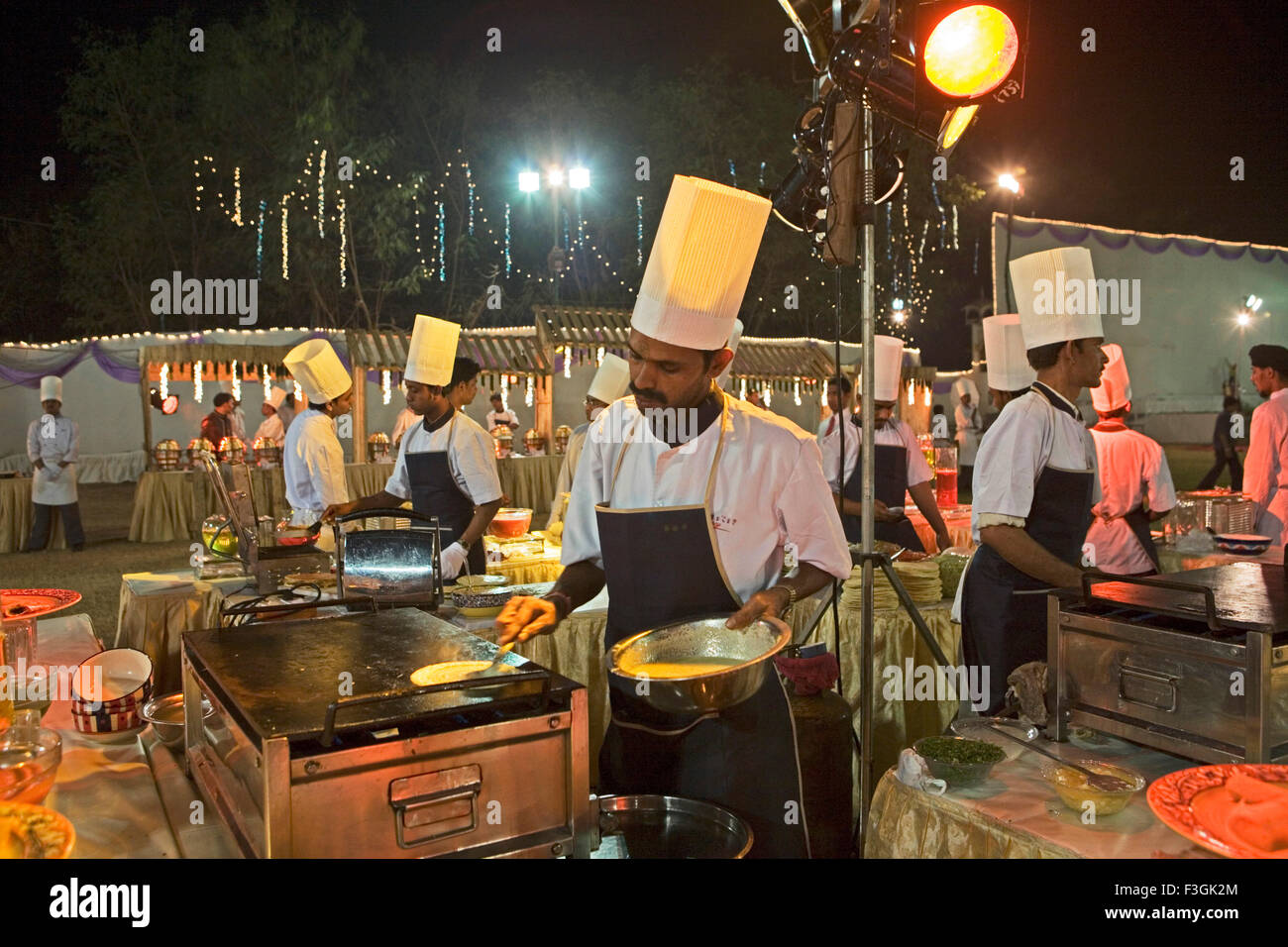 Chefs busy in preparing food for guests at Indian wedding ; Bombay Mumbai ; Maharashtra ; India - Stock Image