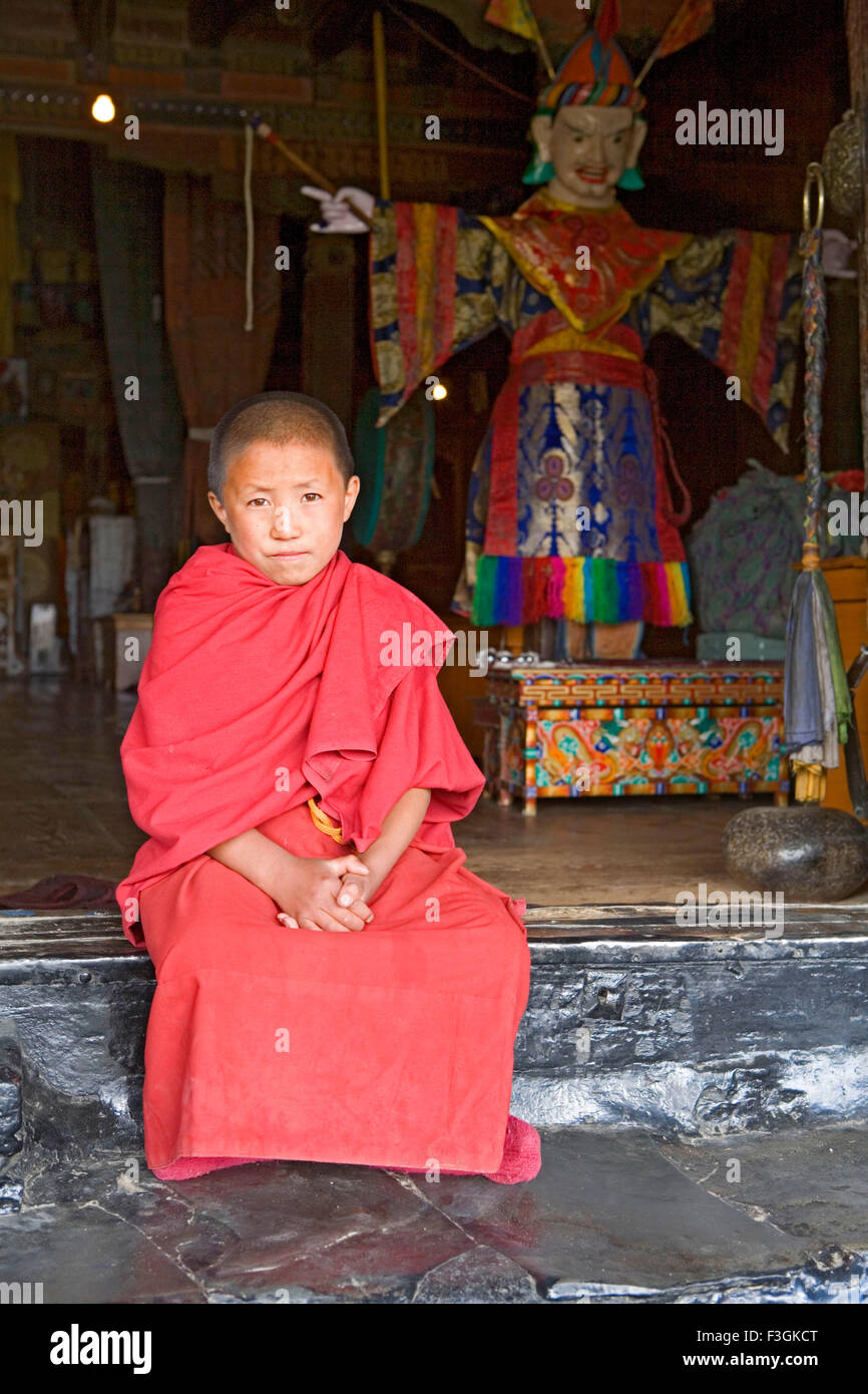 A young lama in his red robes seating outside the temple gate of the Tikse Buddhist Monastery ; Ladakh Jammu and - Stock Image