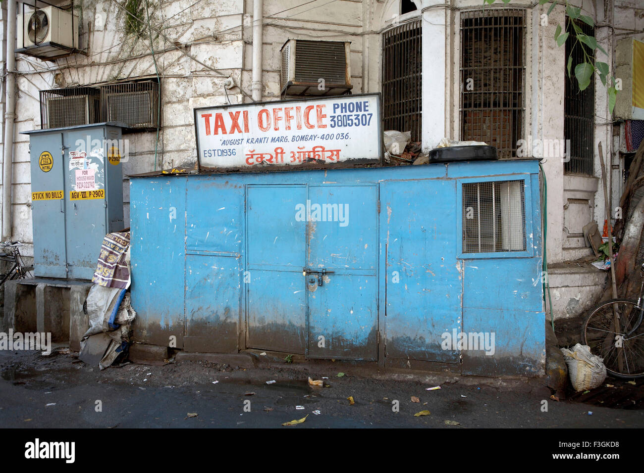 corner building enclosed with a narrow structure serves as an office for taxi operators ; Mumbai Bombay - Stock Image