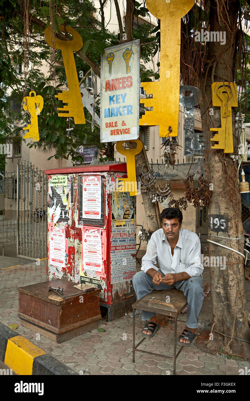 A duplicate key maker setting up his shop under a tree with a display of huge key cutouts to attract customers ; - Stock Image