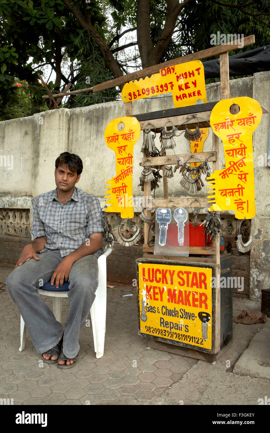 A duplicate key maker with display of huge key cutouts setting up his wares on a footpath ; Mumbai Bombay - Stock Image