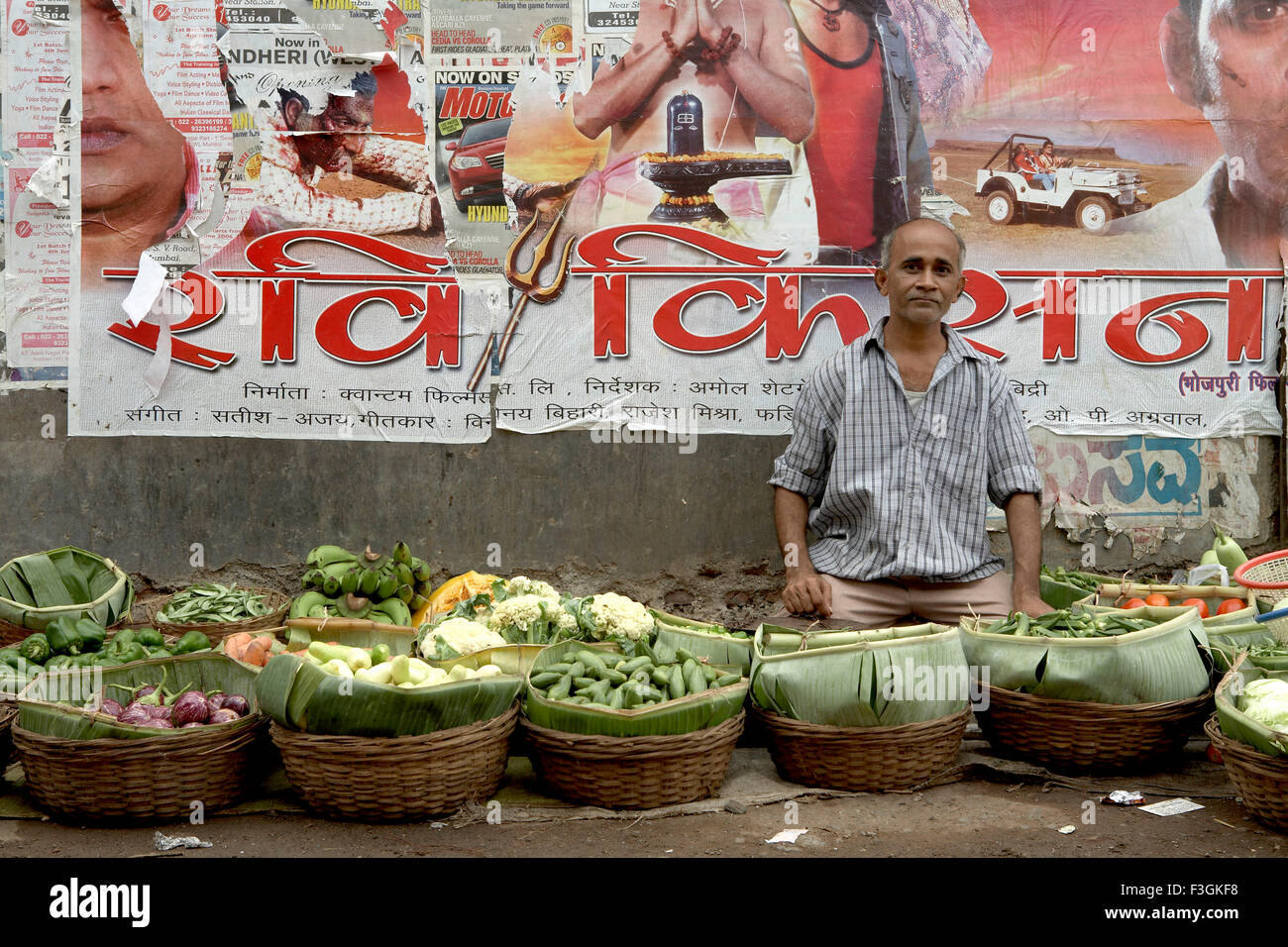 A Bollywood film poster on the wall serves as an interesting backdrop for a vegetable vendor ; Mumbai Bombay - Stock Image