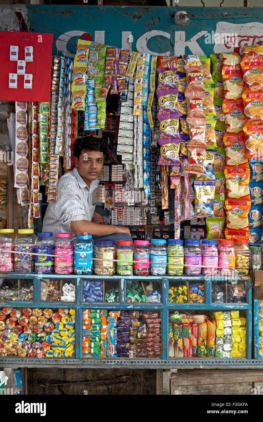 A vendor selling cigarettes ; toffees ; biscuits ; etc neatly and attractively displayed in his small shop ; Mumbai - Stock Image