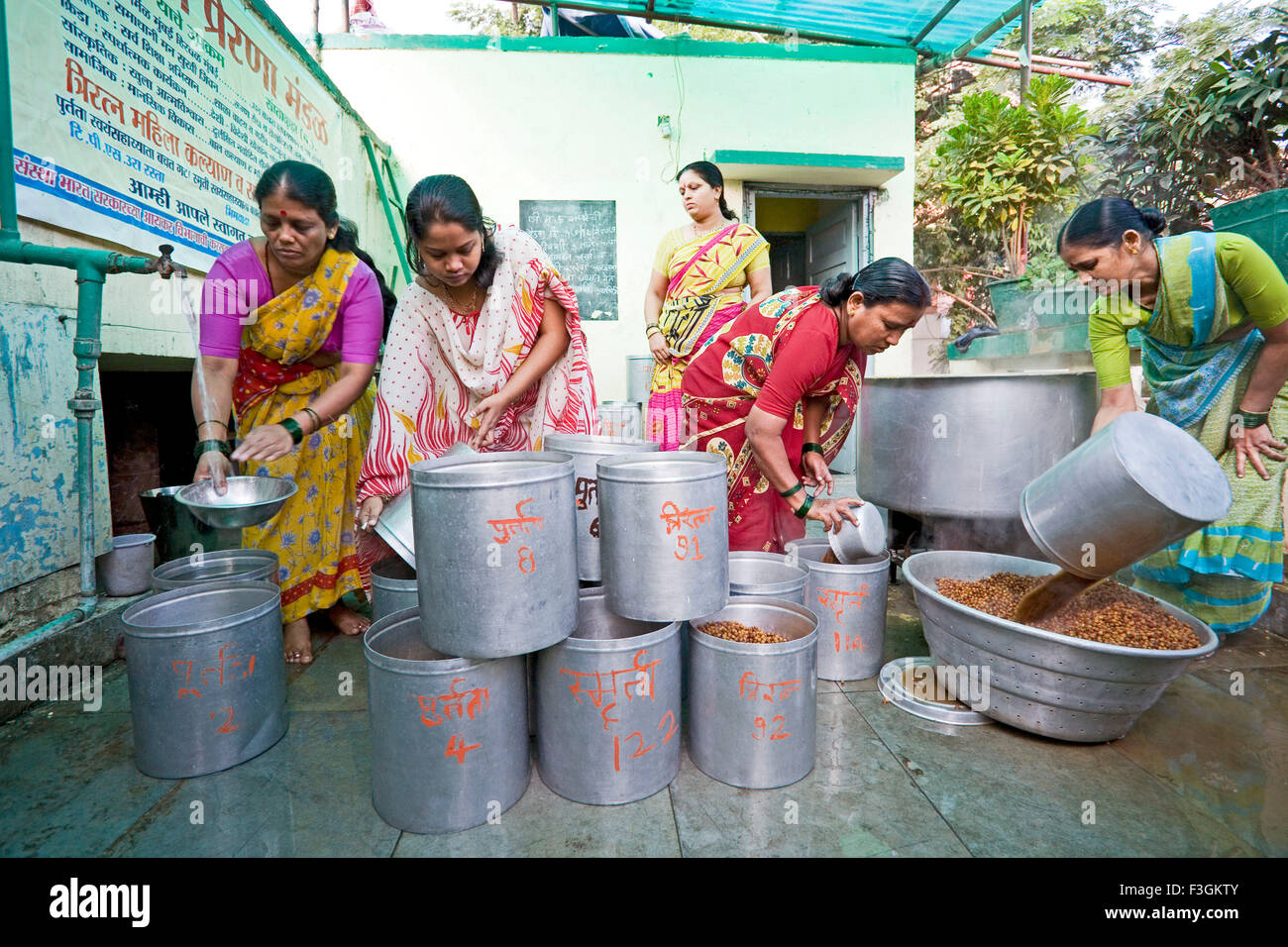 Women employees cook food for children as a part of Government's school mid day meal scheme ; Mumbai ; Maharashtra - Stock Image