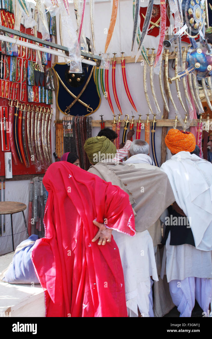 Buyers at sword shop ; Pushkar fair ; Rajasthan ; India - Stock Image