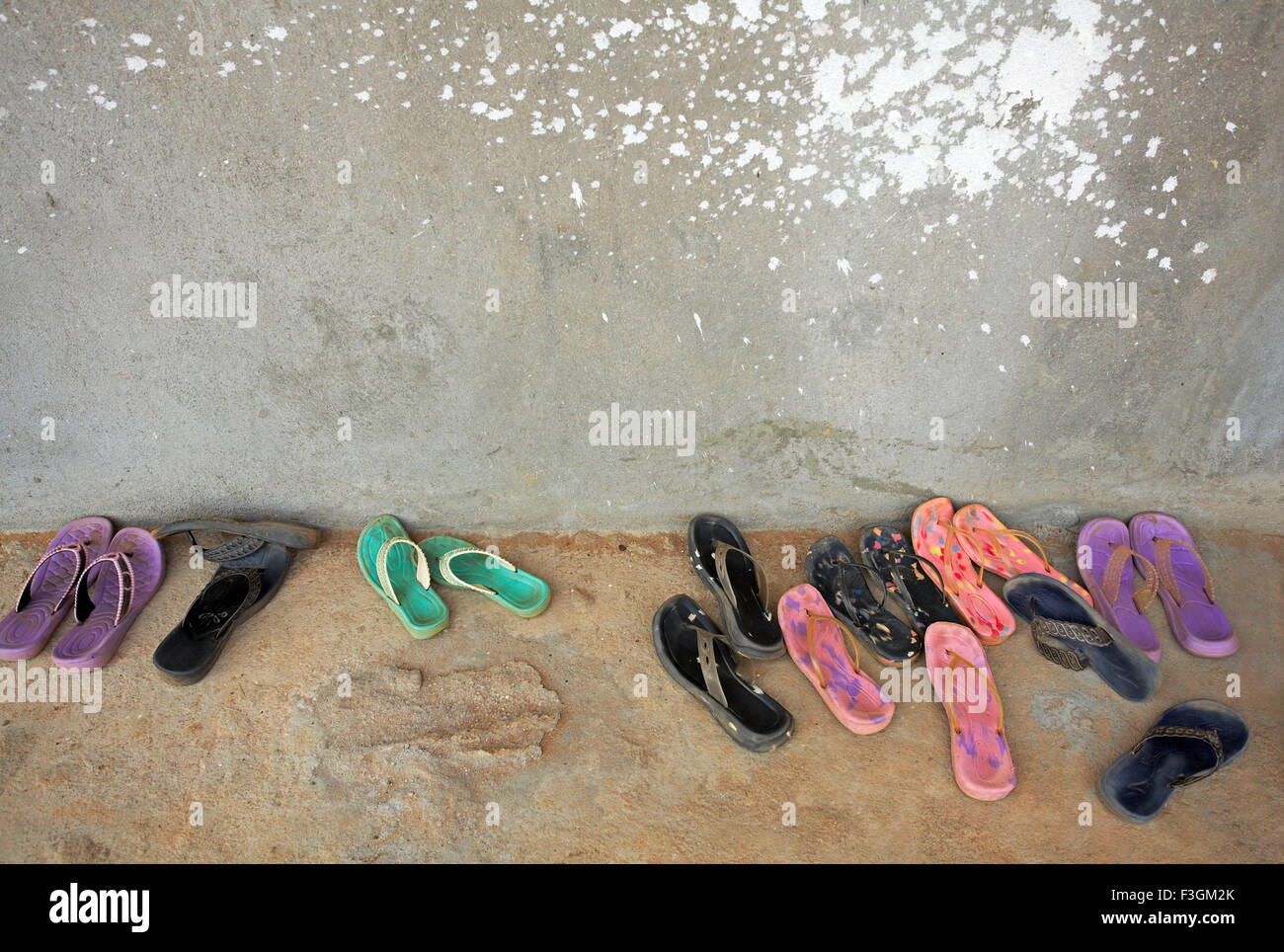 Colourful rubber sleepers of women workers in a row outside a workshop ; Sri Kalahasthi ; Andhra Pradesh ; India - Stock Image
