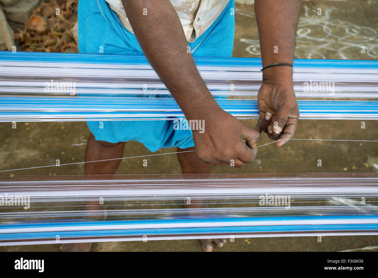 Preparing the textile warp by delicately joining each piece of broken yarn with skilful hands ; Kanchipuram ; Tamil - Stock Image