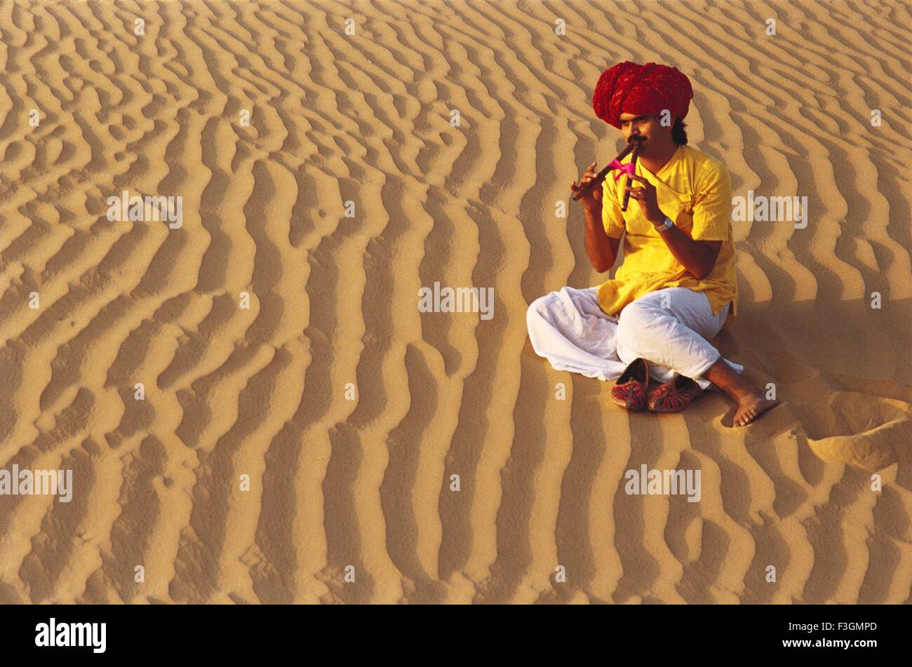 Melody of peace ; rajasthani musician playing algoza sitting on sand ; Rajasthan ; India - Stock Image
