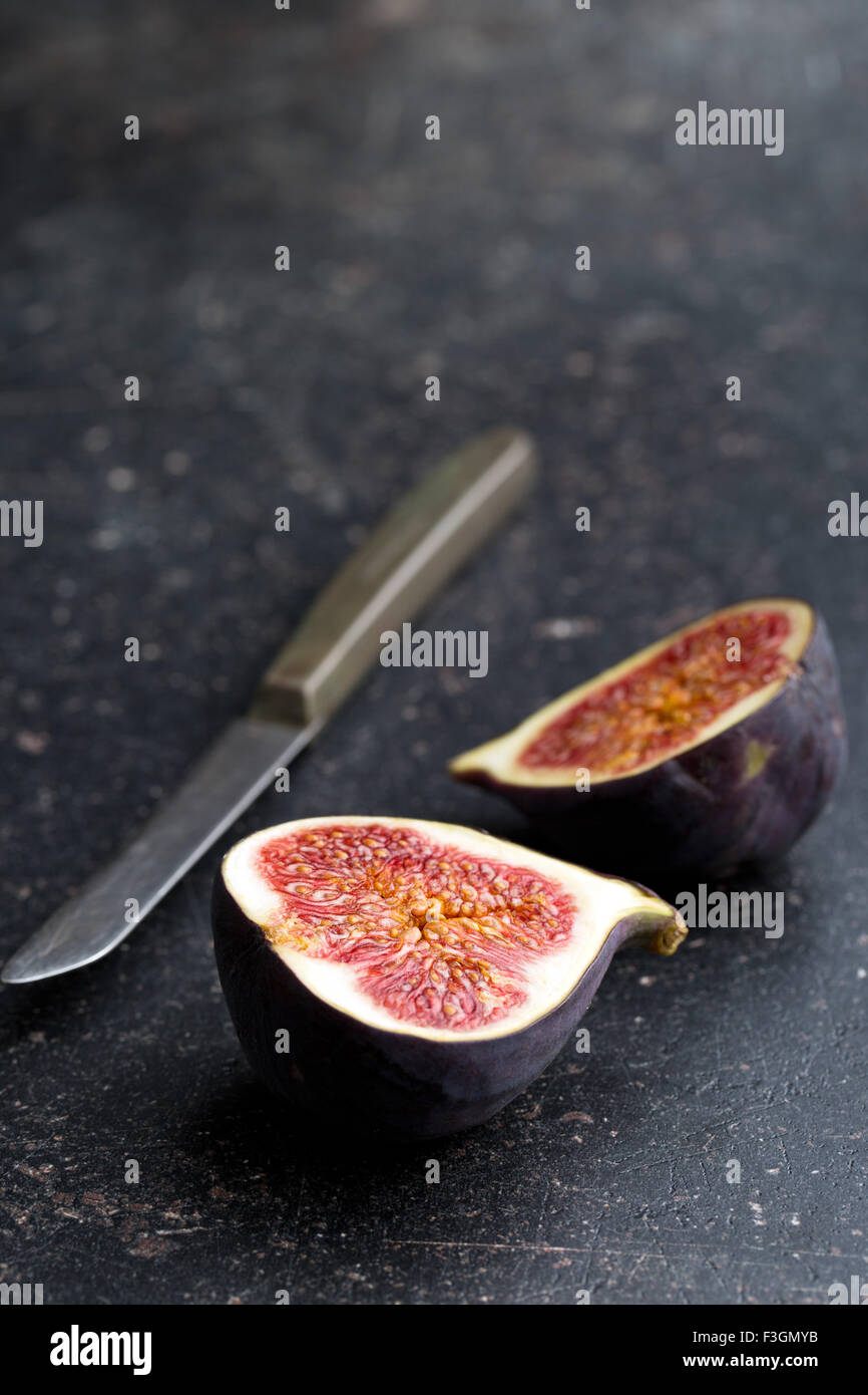 sliced fresh figs on kitchen table - Stock Image