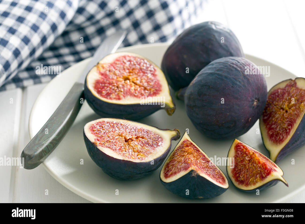 sliced fresh figs on plate with knife - Stock Image