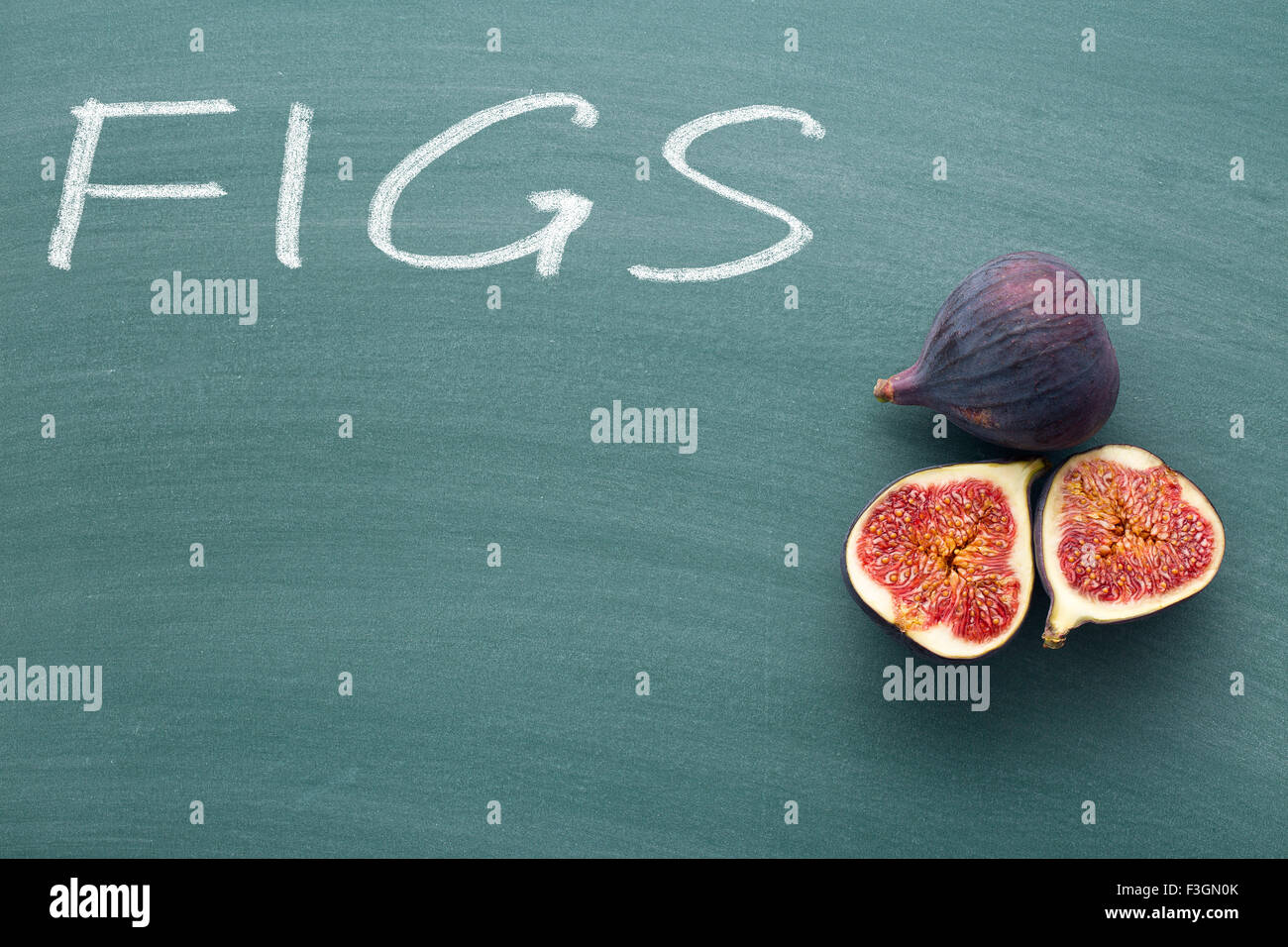 sliced fresh figs on green chalkboard - Stock Image