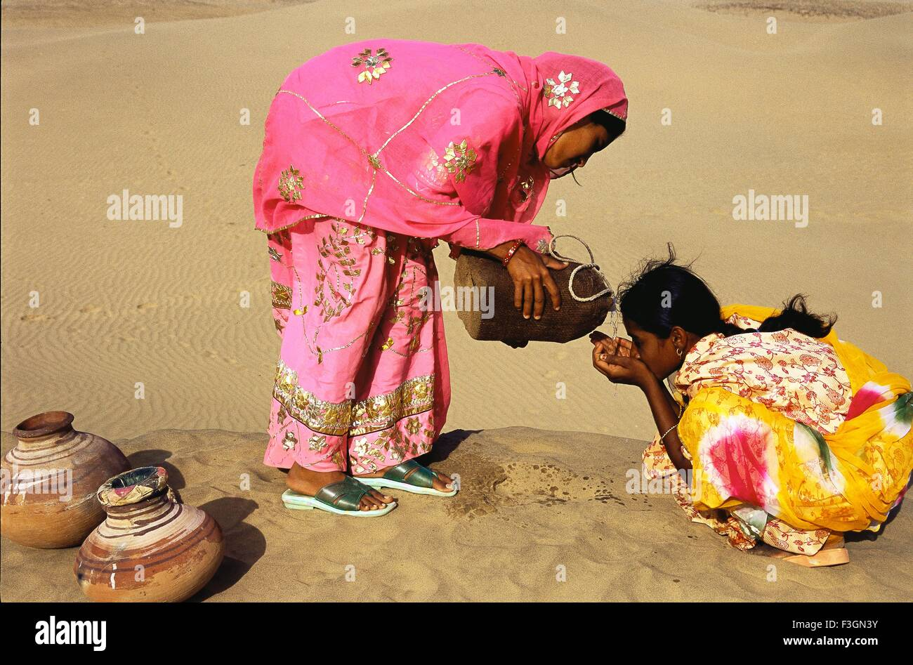 Woman pouring water from leather bag giving to other woman for quenching thirst ; Khuhri ; Jaisalmer ; Rajasthan - Stock Image