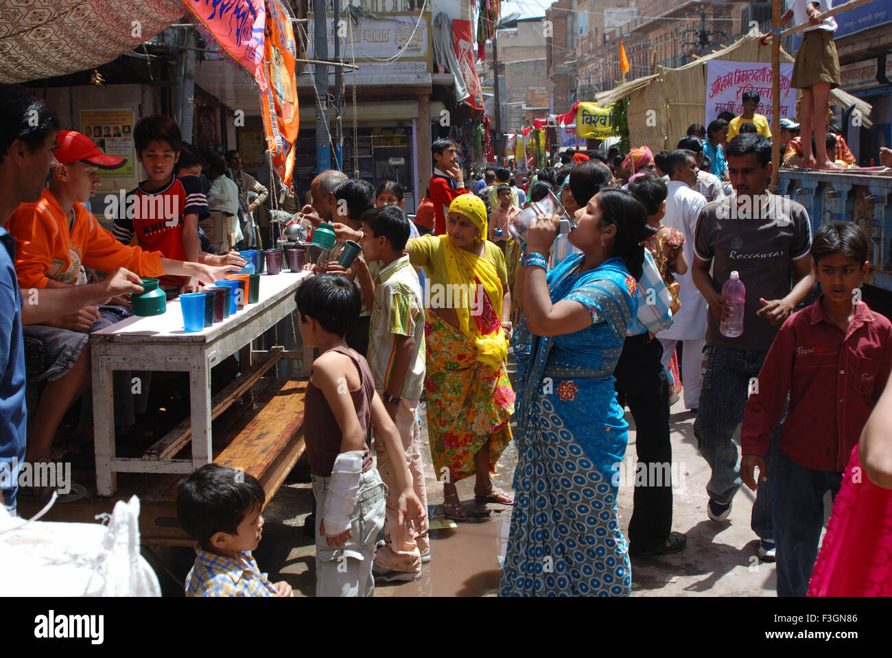 Visitors quenching thirst with cool water in Ramnavmi Procession ; Jodhpur ; Rajasthan ; India - Stock Image