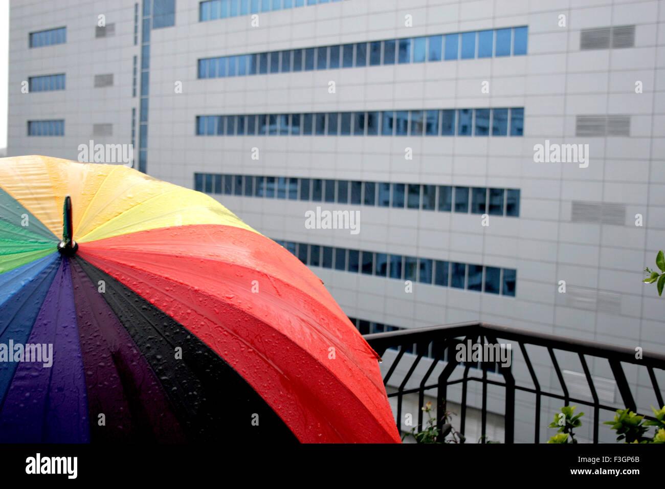 A big sixteen coloured wide open umbrella ; India - Stock Image