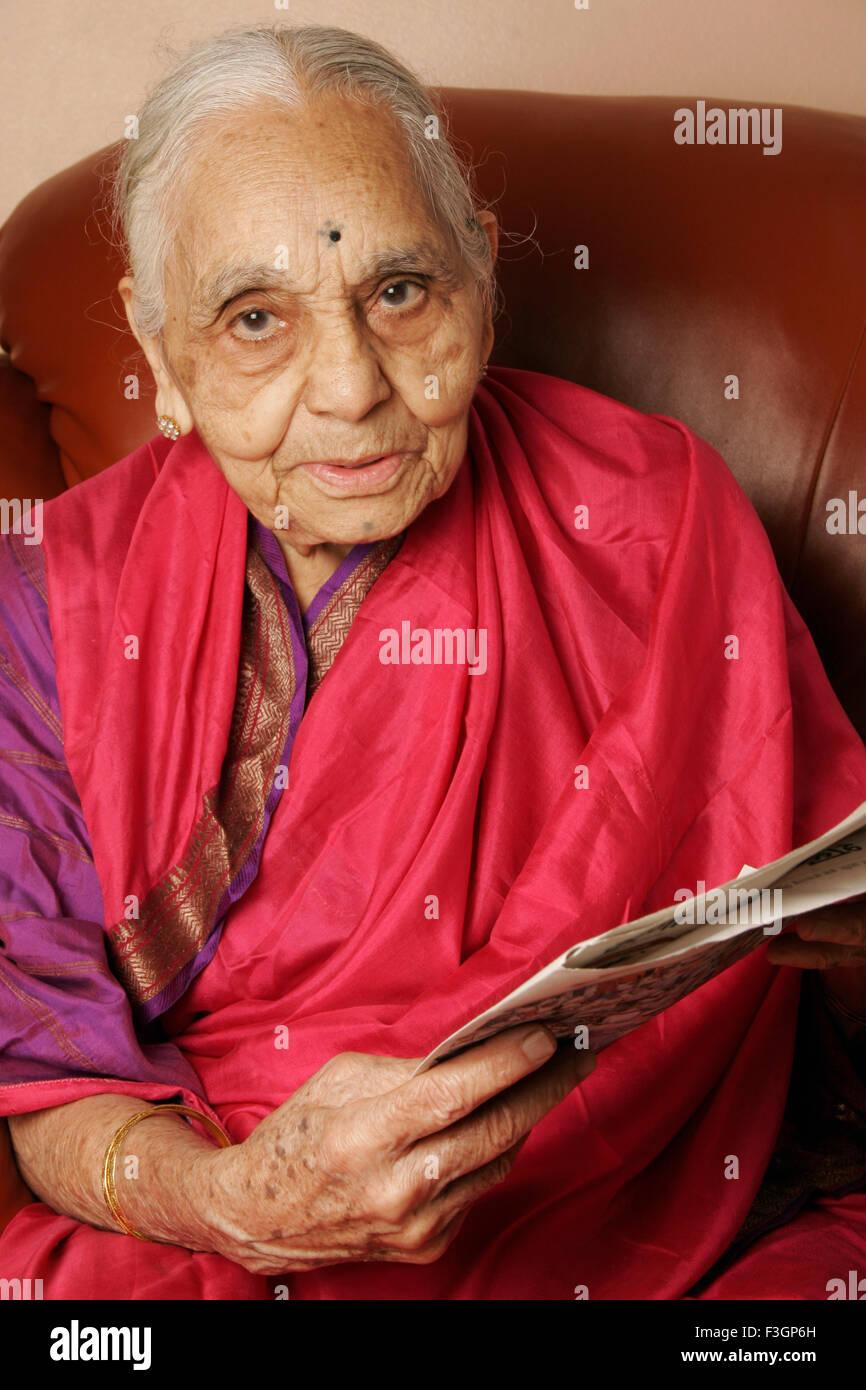A 92 year old Maharashtrian woman reading newspaper ; India MR#686J - Stock Image