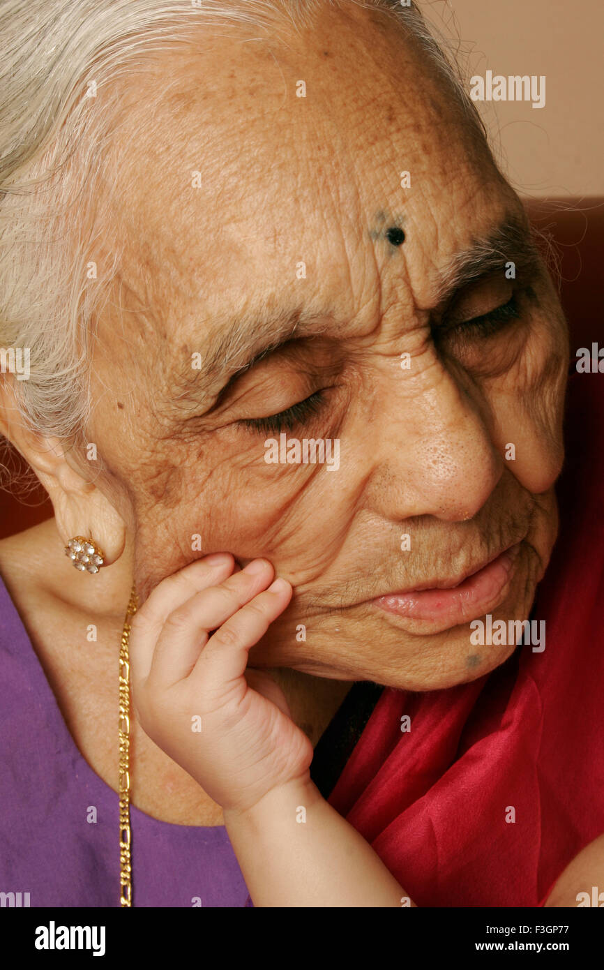 Child pulling the wrinkled and freckled cheek of her 92 year old grand mother ; India MR#686J ; 686K - Stock Image
