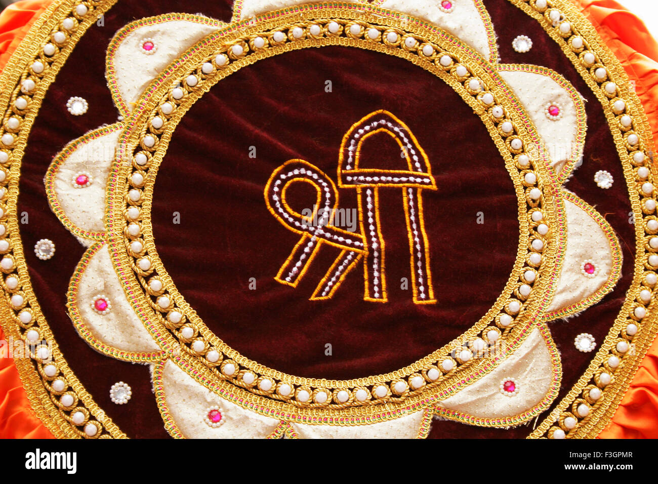 Maroon coloured velvet cloth decorated circular form of golden border and peals Shri mentioned in centre ; Pune - Stock Image