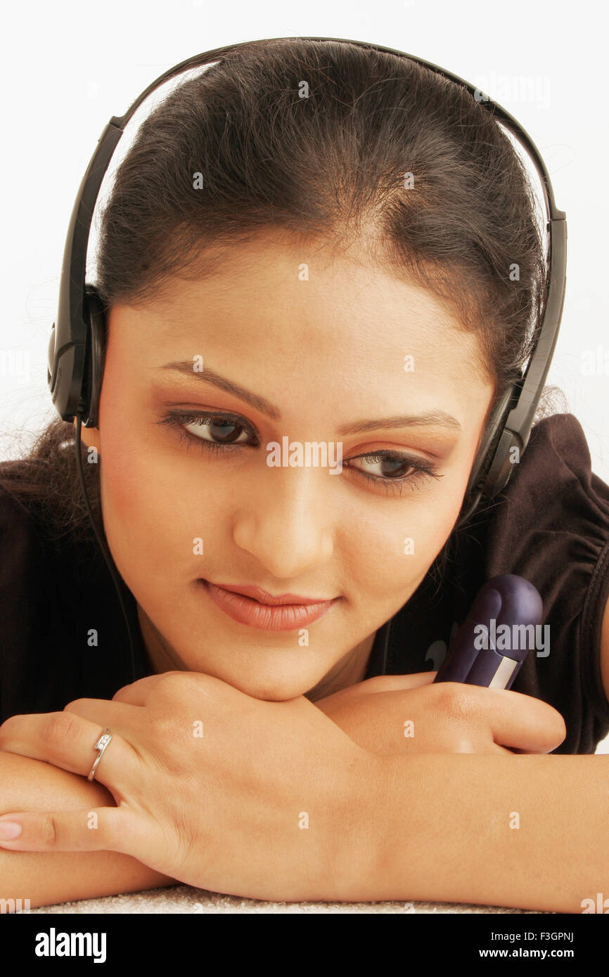 Maharashtrian teenage girl happily engrossed in listening to music using earphones MR#686M - Stock Image