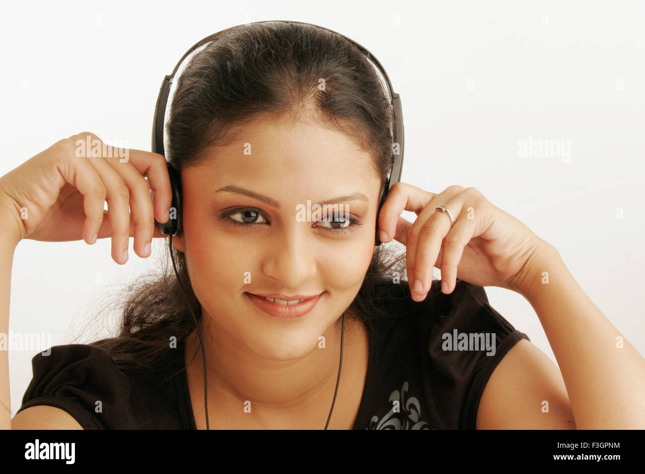 Maharashtrian teenage girl engrossed in listening to music using earphones MR#686M - Stock Image