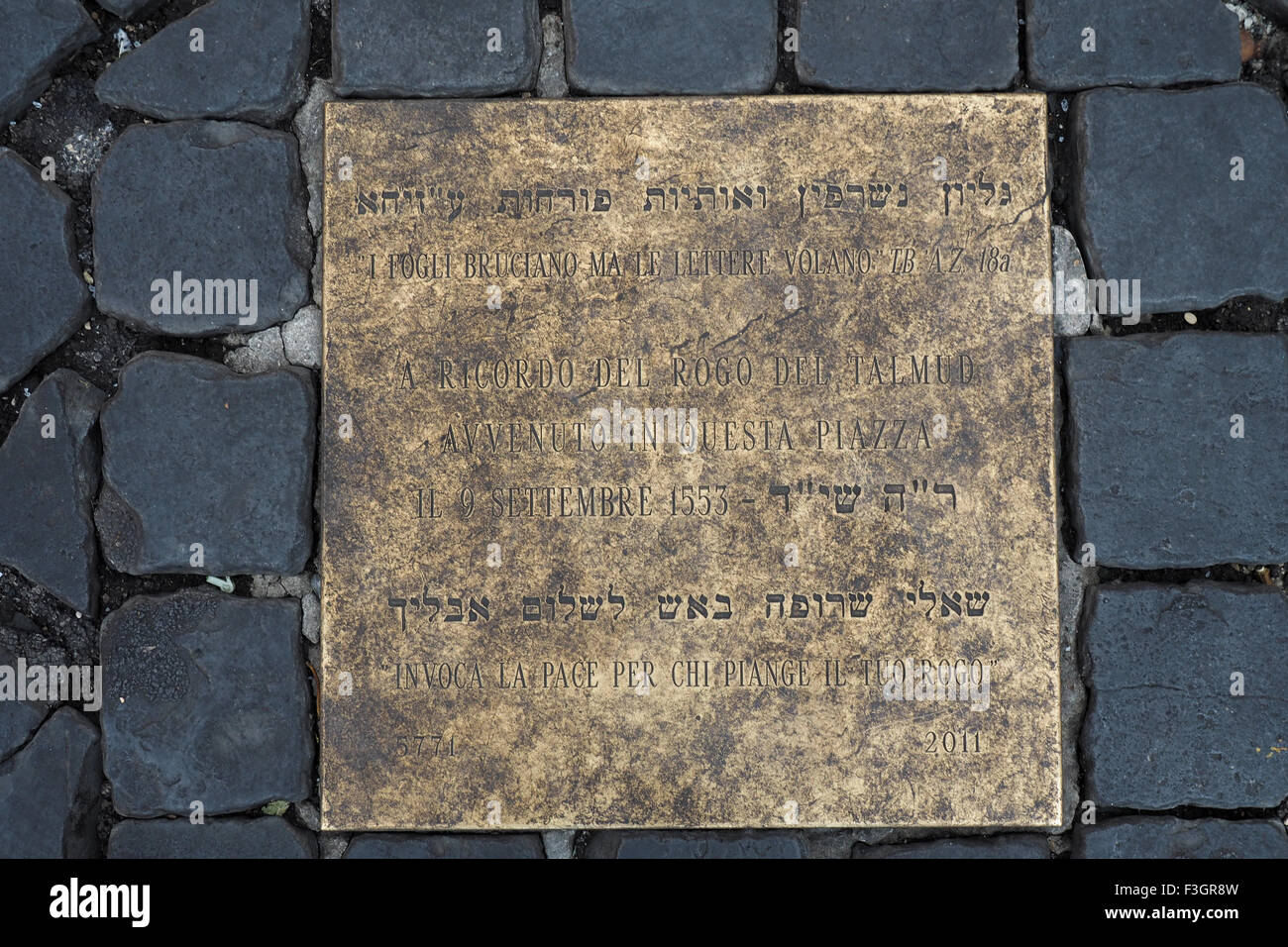 A brass plaque on the ground set in cobblestones. - Stock Image