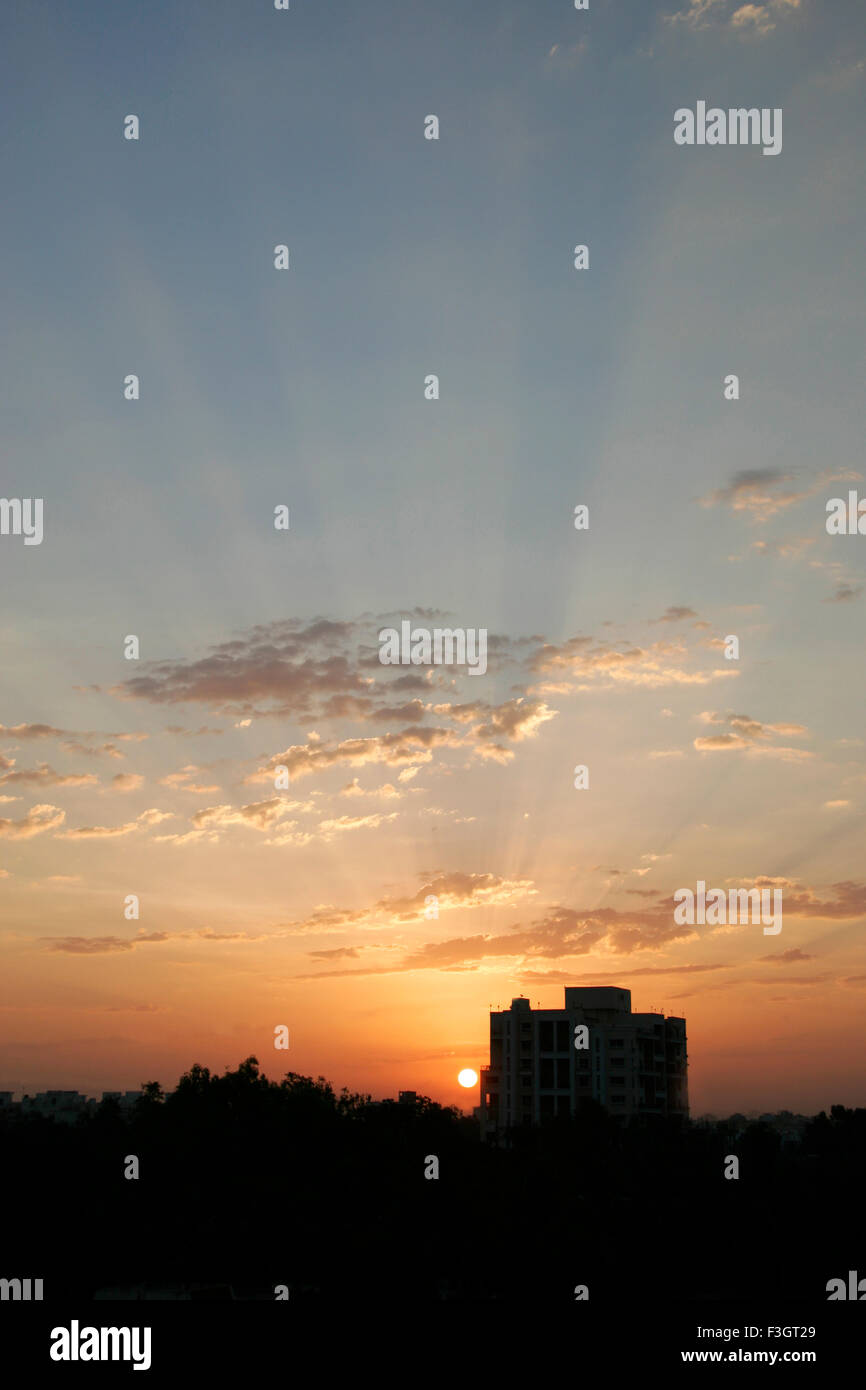 Glorious sunrise behind residential apartment with patchy clouds ; Pune; Maharashtra ; India - Stock Image