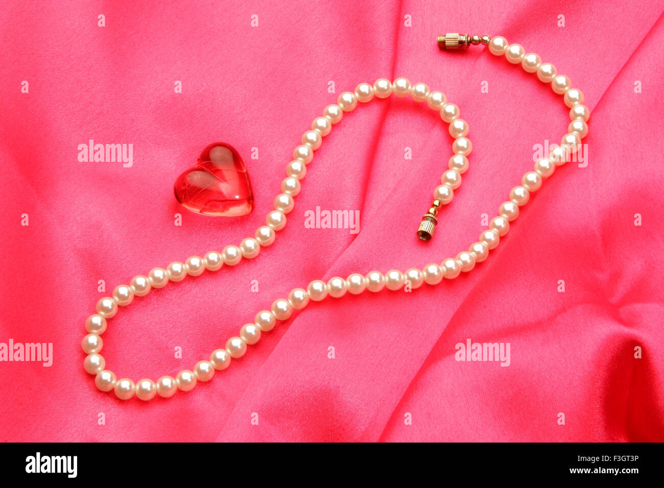 Jewellery in form pearl necklace with synthetic red gem stone of heart shape against pink satin background - Stock Image