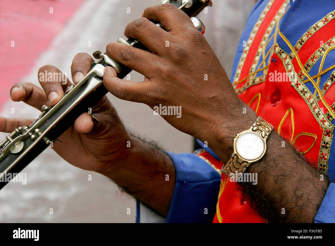 Hands of flute player bajawalawear watch played immersion festival lord Ganesh Pune Maharashtra - Stock Image