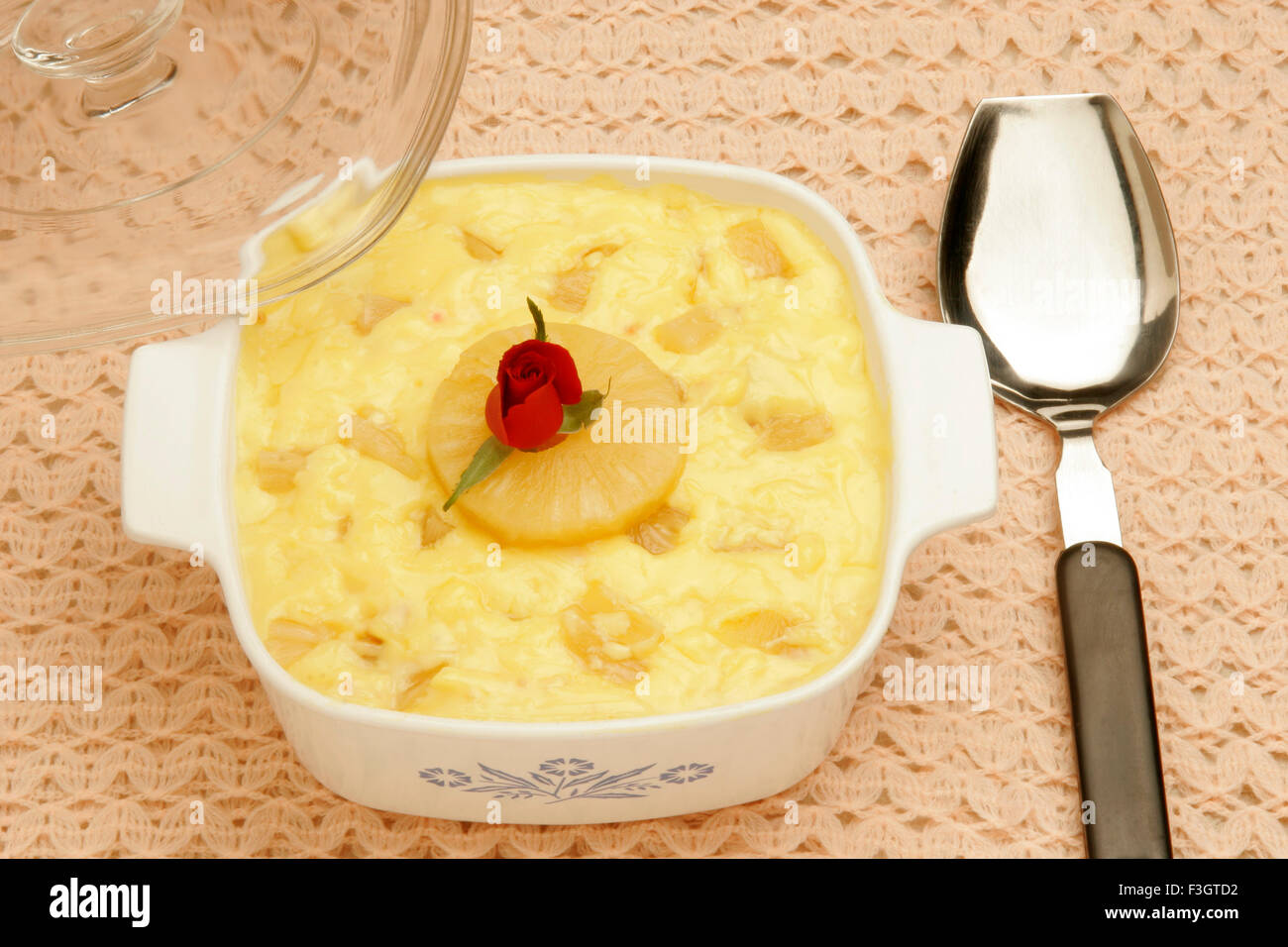 Pudding made song cake vanilla custard and pineapple pieces glass lid red rose centre serving spoon served lunch - Stock Image