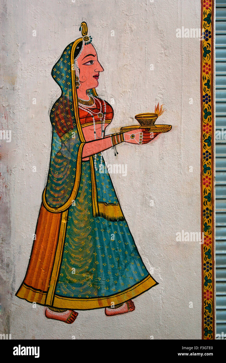 Wall painting depicting lady walking with light called diya in her palms ; Nathdwara ; Rajasthan ; India - Stock Image