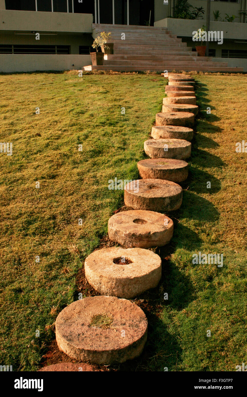 Round stones laid green grass in row in form of entrance of house as d'cor ; Pune ; Maharashtra ; India - Stock Image