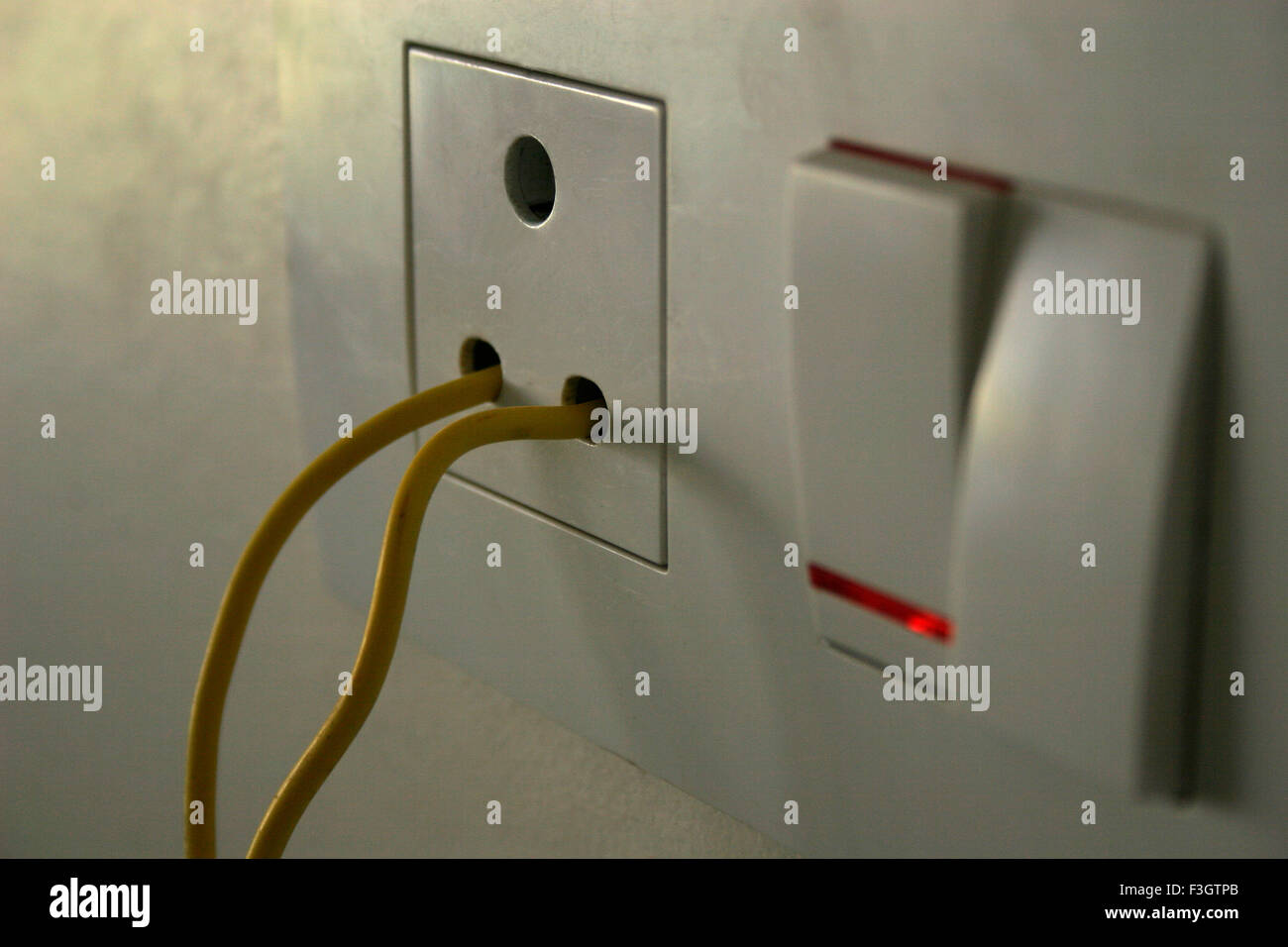 Yellow electric wire inserted in socket without plug and with switch ...