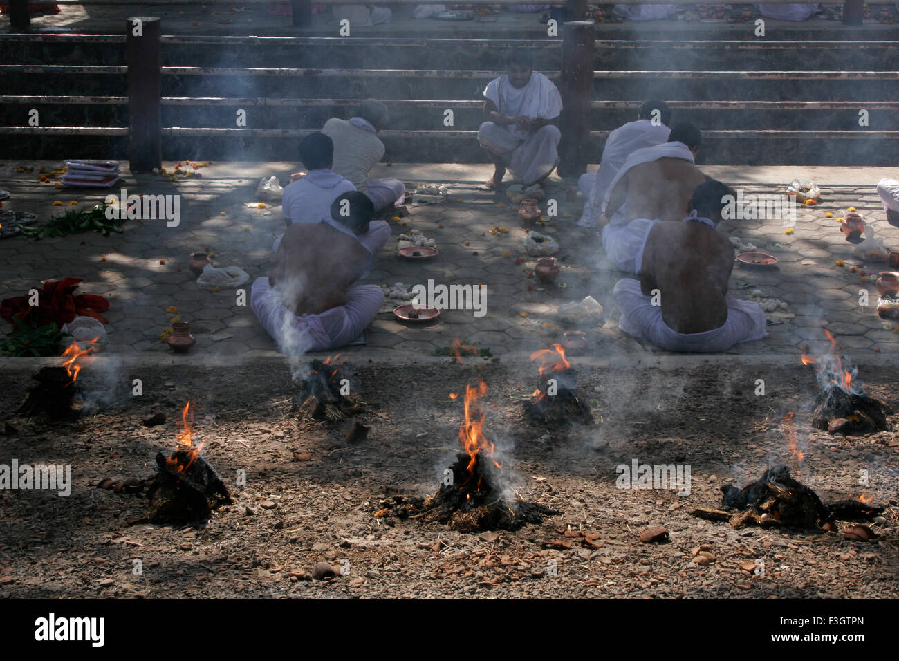 Traditional and customary ceremonies called Shraad Puja performed by seven Indian men amidst fire smoke beloved - Stock Image