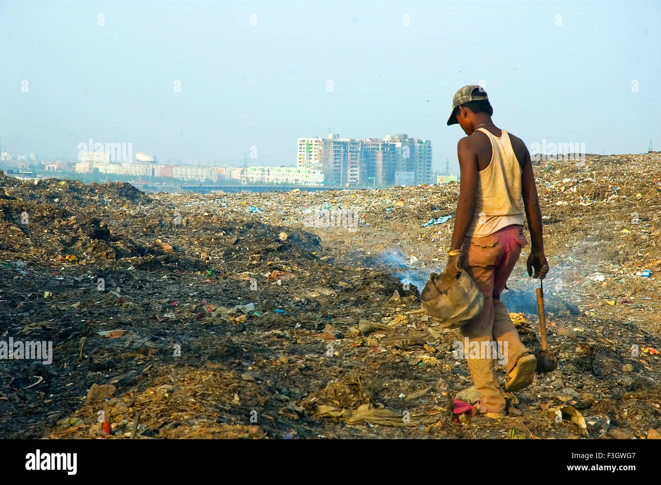 Garbage collector boy looking for metal scrap from waste scrap on Gazipur dumping ground ; Delhi ; India - Stock Image