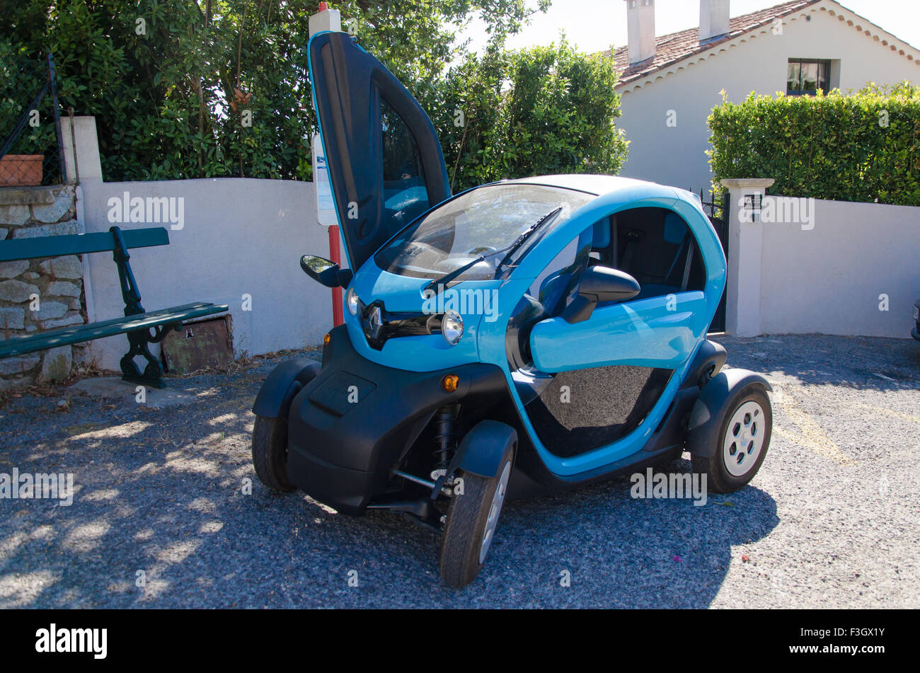 Blue twizy parked in front of a house with an open door Stock Photo