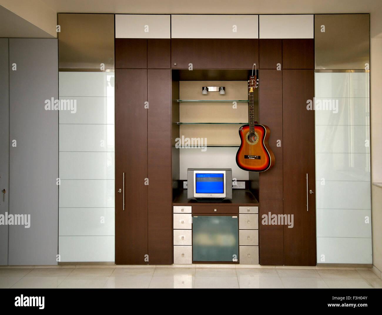 Interior of house ; television with guitar ; Mulund ; Bombay Mumbai ; Maharashtra ; India Stock Photo