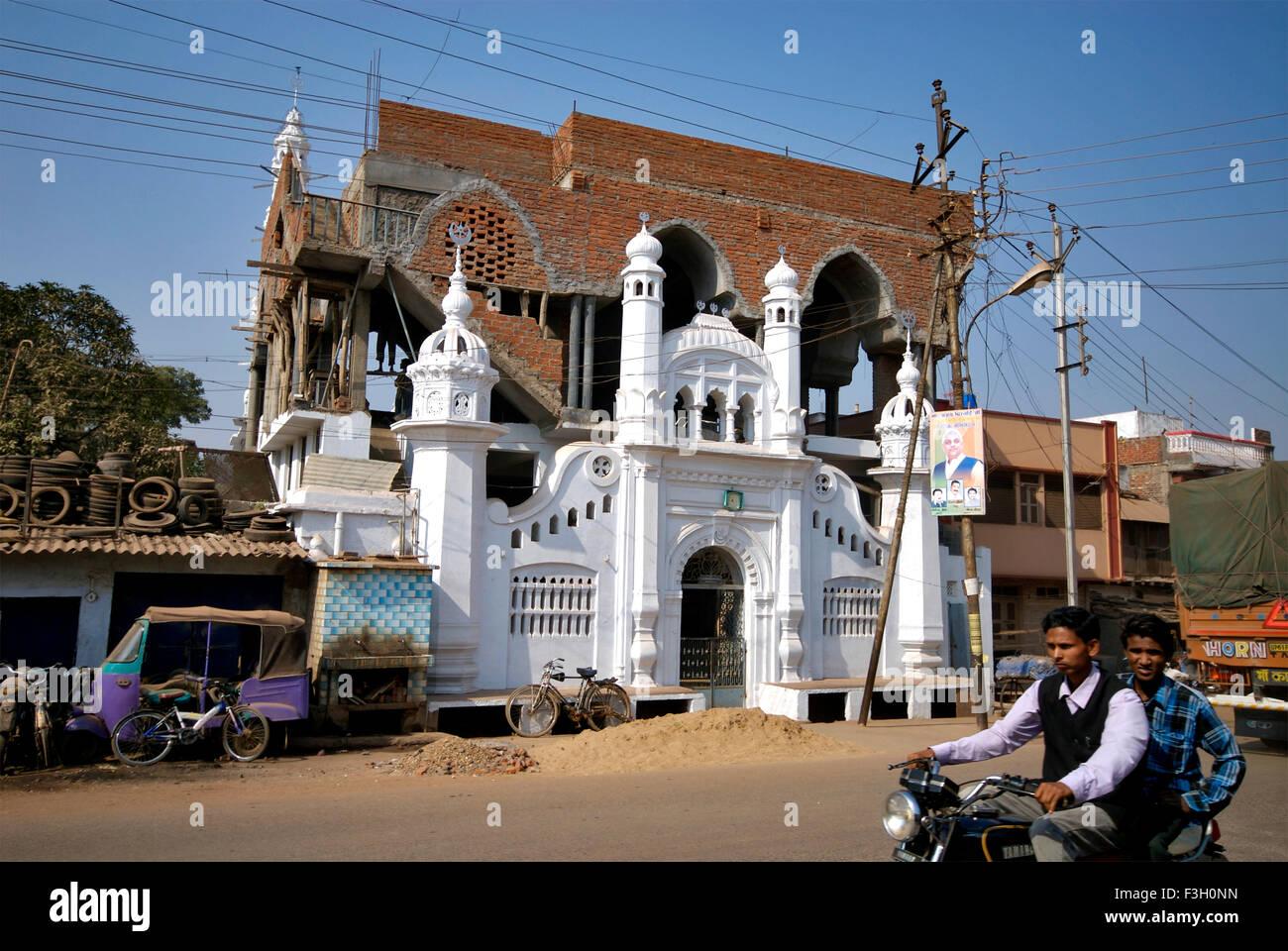 Motorcycle riders ride past at construction site of Mosque ; Katni ; Madhya Pradesh ; India - Stock Image