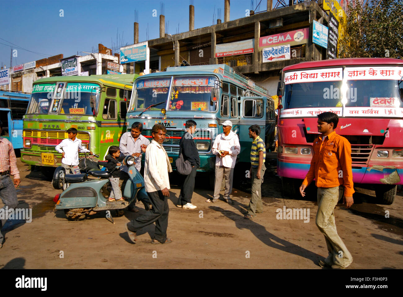 People walk past buses at Bus stop ; Jabalpur ; Madhya Pradesh ; India - Stock Image