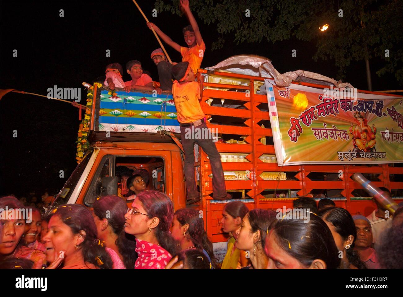 Women walking past a truck at ganesh visarjan - Stock Image