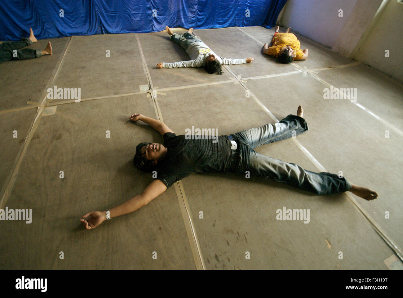 People performing a relaxing exercise during an acting workshop ; Nanhi Duniya school ; Dehradun ; Uttaranchal ; - Stock Image