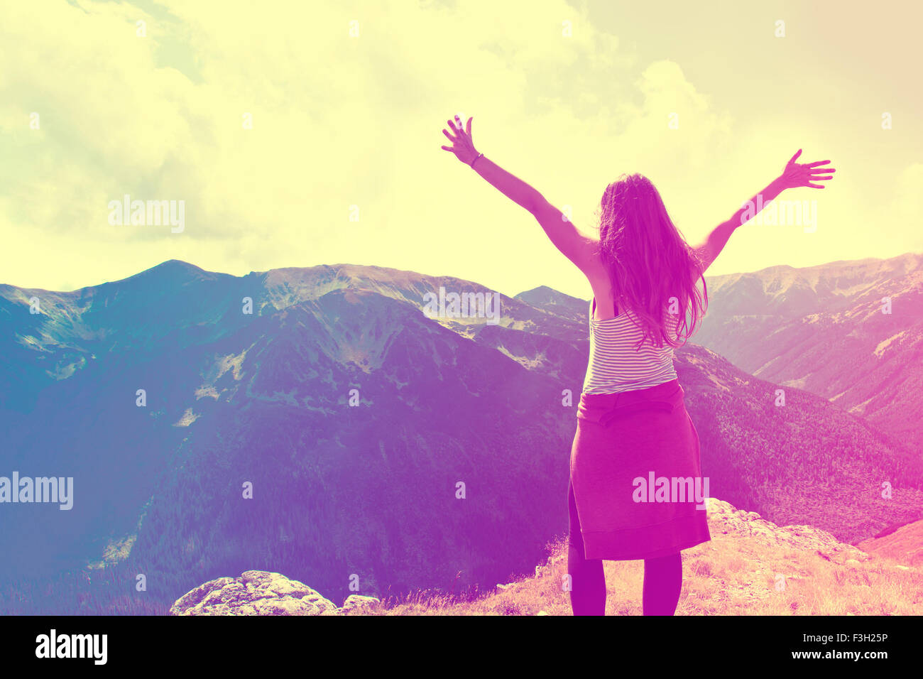 Happy teenage girl feel freedom in mountains scenery. Vintage instagram picture. - Stock Image