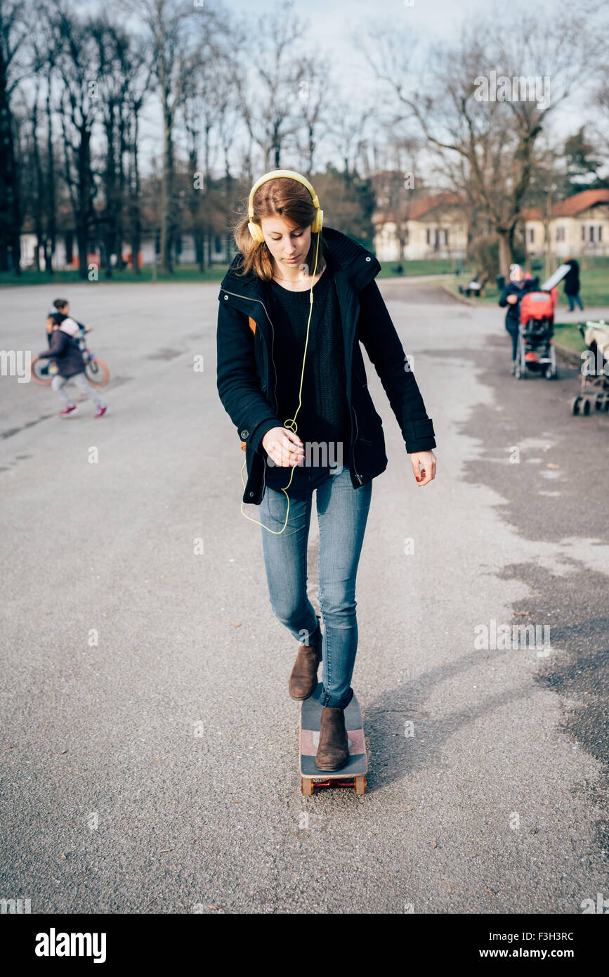 young beautiful hipster sporty blonde woman skating in a city park, listening music with headphones, looking downward - Stock Image